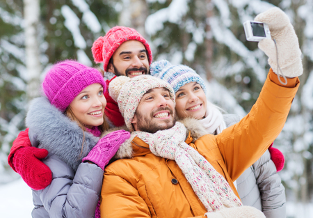 technology, season, friendship and people concept - group of smiling men and women taking selfie with digital camera in winter forest photo