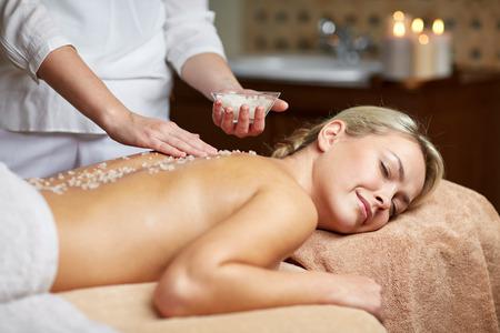 massieren: Menschen, Sch�nheit, Spa, Massage und Entspannung Konzept - Nahaufnahme der sch�nen jungen Frau mit geschlossenen Augen und Therapeuten halten Salz Sch�ssel in Spa-Liegen Lizenzfreie Bilder