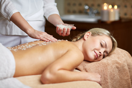 therapeutic: people, beauty, spa, massage and relaxation concept - close up of beautiful young woman lying with closed eyes and therapist holding salt bowl in spa