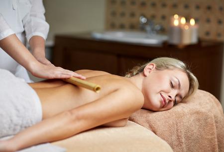 massage: Menschen, Schönheit, Spa, gesunden Lebensstil und Entspannung Konzept - Nahaufnahme der schönen jungen Frau mit geschlossenen Augen liegt und Bambus-Massage im Spa-