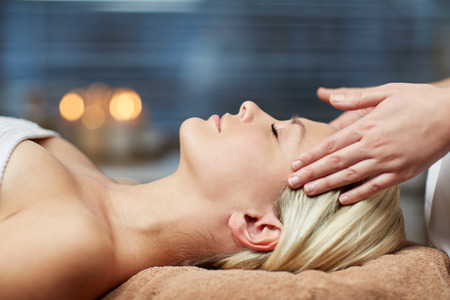spa: people, beauty, spa, healthy lifestyle and relaxation concept - close up of beautiful young woman lying with closed eyes and having face or head massage in spa Stock Photo