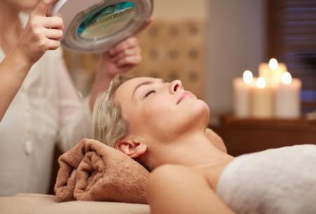 masajes faciales: personas, belleza, spa, estilo de vida saludable y la relajaci�n concepto - cerca de la hermosa mujer joven tendido con los ojos cerrados y cosmet�loga que buscan a trav�s de aumento de la l�mpara en el spa Foto de archivo