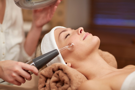 massager: people, beauty, spa, cosmetology and technology concept - close up of beautiful young woman lying with closed eyes having face massage by massager in spa