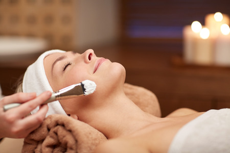 facial cleansing: people, beauty, spa, cosmetology and skincare concept - close up of beautiful young woman lying with closed eyes and cosmetologist applying facial mask by brush in spa
