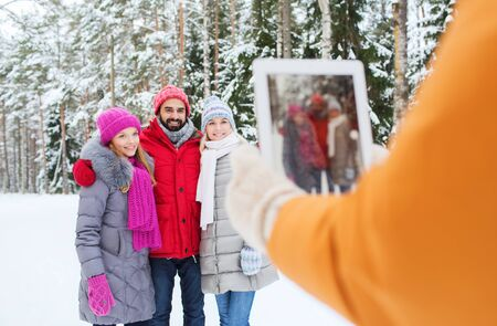 photographing: technology, season, friendship and people concept - group of smiling men and women taking picture with tablet pc computer in winter forest