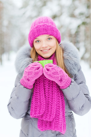 season, christmas, drinks and people concept - happy smiling young woman with cup drinking hot tea in winter forest photo
