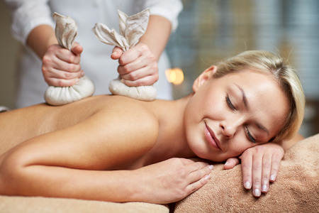 people, beauty, spa, healthy lifestyle and relaxation concept - close up of beautiful young woman lying and having herbal bag massage in spa Stock Photo
