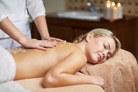 therapeutic: people, beauty, spa, healthy lifestyle and relaxation concept - close up of beautiful young woman lying with closed eyes and having salt massage l in spa