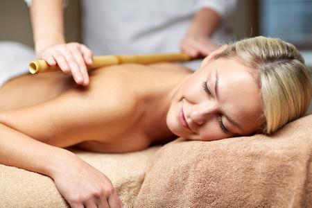 bambou: gens, beauté, spa, mode de vie sain et de détente notion - close up de la belle jeune femme allongée, les yeux fermés et ayant massage au bambou dans le spa