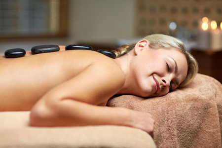 therapeutic: people, beauty, spa, healthy lifestyle and relaxation concept - close up of beautiful young woman having hot stone massage in spa Stock Photo