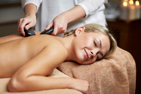 masajes relajacion: personas, belleza, spa, estilo de vida saludable y la relajaci�n concepto - cerca de la hermosa mujer joven que tiene masaje con piedras calientes en el spa