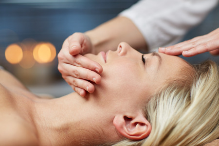 treatment: people, beauty, spa, healthy lifestyle and relaxation concept - close up of beautiful young woman lying with closed eyes and having face or head massage in spa Stock Photo