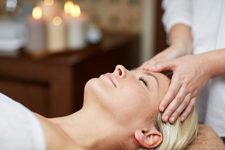 people, beauty, spa, healthy lifestyle and relaxation concept - close up of beautiful young woman lying with closed eyes and having face or head massage in spa Stock Photo