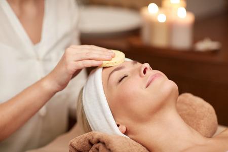 les gens, la beauté, un spa, de la cosmétologie et de détente notion - close up de la belle jeune femme allongée les yeux fermés ayant nettoyage de visage en éponge dans le spa