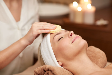 people, beauty, spa, cosmetology and relaxation concept - close up of beautiful young woman lying with closed eyes having face cleaning by sponge in spa Standard-Bild