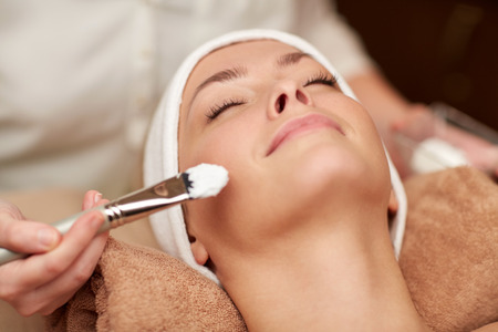 cosmetologist: people, beauty, spa, cosmetology and skincare concept - close up of beautiful young woman lying with closed eyes and cosmetologist applying facial mask by brush in spa