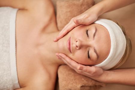 mensen, beauty, spa, cosmetica en ontspanning concept - close-up van mooie jonge vrouw, liggend met gesloten ogen die het gezicht massage in de spa