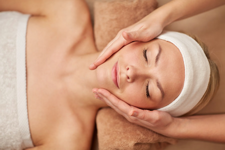 people, beauty, spa, cosmetology and relaxation concept - close up of beautiful young woman lying with closed eyes having face massage in spa Stock Photo