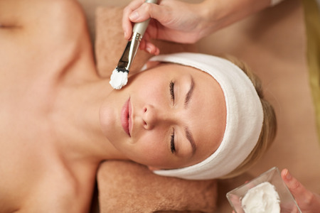 masaje facial: personas, belleza, spa, cosmetolog�a y cuidado de la piel concepto - cerca de la hermosa mujer joven tendido con los ojos cerrados y cosmet�loga que aplican la m�scara facial con brocha en el spa