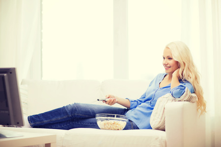 snack time: food, happiness and people concept - smiling young girl with popcorn watching movie at home Stock Photo