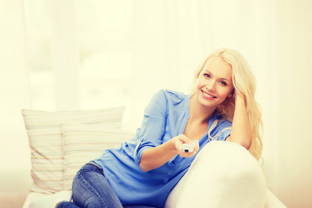 sitting pretty: television, relax, home and happiness concept - smiling young girl sitting on couch with tv remote control at home Stock Photo