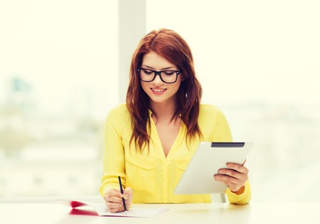 business, education and technology concept - smiling student in eyeglasses with tablet pc computer and notebook in college photo