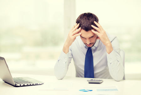 financial crisis: office, business, technology, finances and internet concept - stressed businessman with laptop computer and documents at office Stock Photo