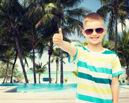 pool preteen: childhood, travel, summer vacation, gesture and people concept - smiling little boy wearing sunglasses over beach background