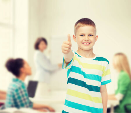 childhood, school, education and people concept - smiling little boy showing thumbs up over group of students in classroom photo