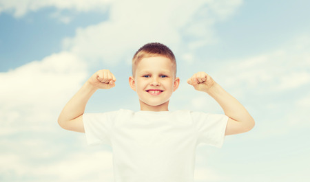 advertising, ecology, people and childhood concept - smiling little boy in white blank t-shirt flexing biceps over blue sky background photo
