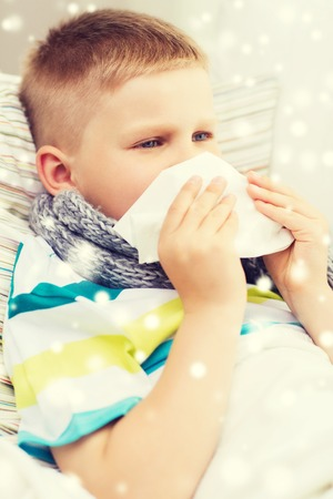 grippe: childhood, healthcare and people concept - ill boy with flu blowing nose into tissue at home
