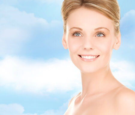 people, beauty and health care concept - close up of smiling young woman over blue sky background photo
