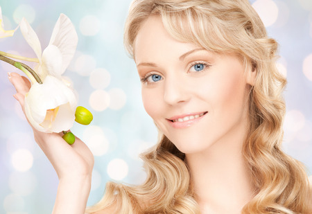 cabello rubio: la belleza y el concepto de la gente - la cara de la mujer hermosa joven con la flor sobre luces azul de fondo Foto de archivo
