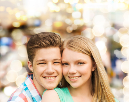 teenage couple: holidays, vacation, love and people concept - smiling teenage couple hugging over holiday lights background