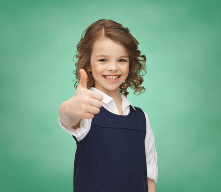 people, gesture, children, school and happiness concept happy little school girl showing thumbs up over green chalk board photo