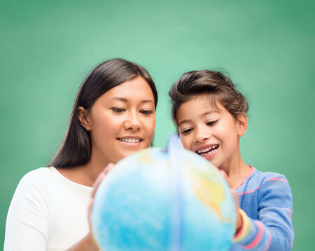 children, education, school and happy people concept - happy teacher and little schoolgirl with globe over green chalk board background photo