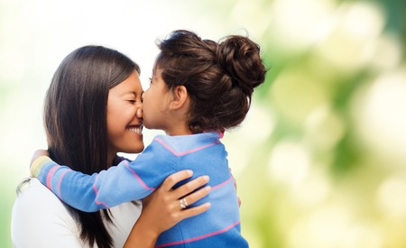 asian child: family, children and happy people concept - happy little girl hugging and kissing her mother over green background