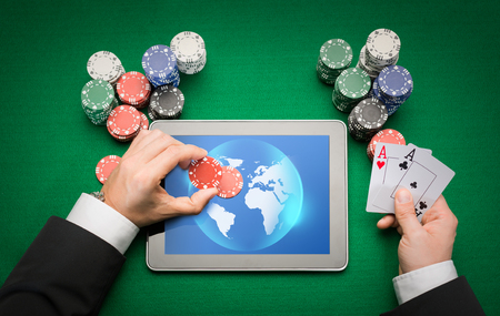 online casino, worldwide gambling, technology and people concept - close up of poker player with playing cards, tablet pc computer and chips at green casino table photo