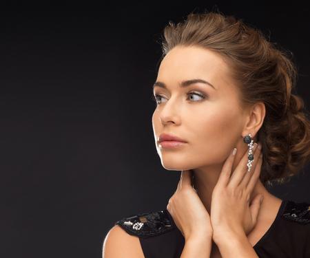 beautiful woman in evening dress wearing diamond earrings photo
