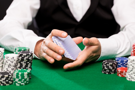 cards deck: casino, gambling, poker, people and entertainment concept - close up of holdem dealer shuffling playing cards deck and chips on green table Stock Photo