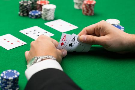 カジノ、火かき棒、人々、エンターテイメントの概念 - はトランプと緑のカジノ テーブルでチップ ポーカー プレーヤーのクローズ アップ 写真素材
