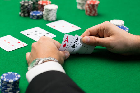 texas hold'em: casino, gambling, poker, people and entertainment concept - close up of poker player with playing cards and chips at green casino table