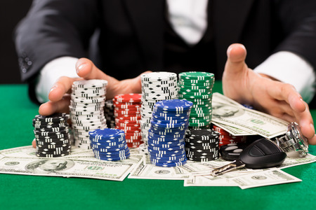 texas hold'em: casino, gambling, people and entertainment concept - close up of poker player with chips, money and personal stuff at green casino table