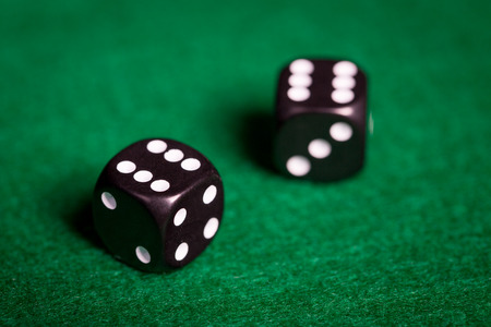 double the chances: gambling, fortune, game and entertainment concept - close up of black dice with double six on green casino table Stock Photo