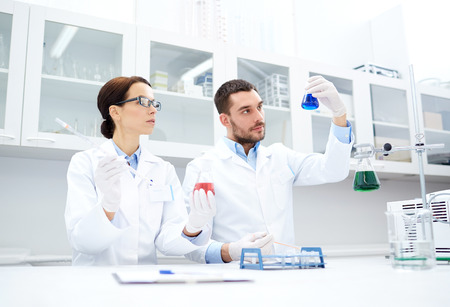 discovering: science, chemistry, technology, biology and people concept - young scientists with pipette and flask making test or research in clinical laboratory