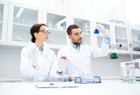 wetenschap, chemie, technologie, biologie en mensen concept - jonge wetenschappers met een pipet en kolf making test of het onderzoek in de klinische laboratorium