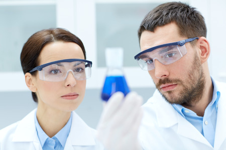 biology: science, chemistry, research, biology and people concept - young scientists holding flask with medicine or chemical in clinical laboratory