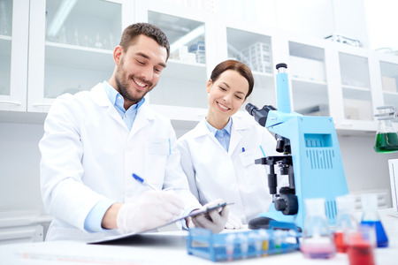 discovering: science, chemistry, technology, biology and people concept - young scientists with microscope making test or research in clinical laboratory and taking notes