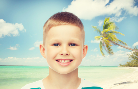 preteens beach: childhood, summer, travel, vacation and people concept - smiling little boy over beach background
