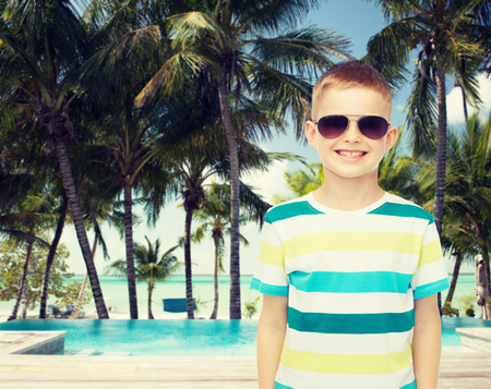 pool preteen: childhood, summer, travel, vacation and people concept - smiling little boy wearing sunglasses over pool and beach background
